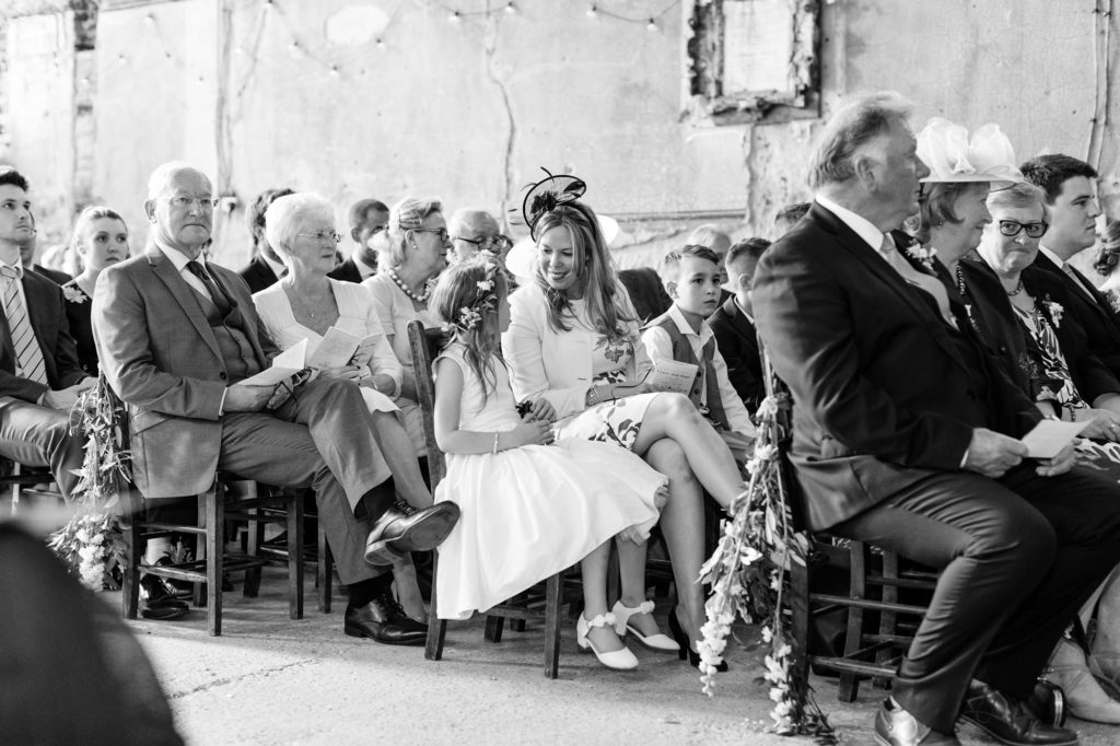 Little flower girl and mother smile at each other during ceremony at Asylum.