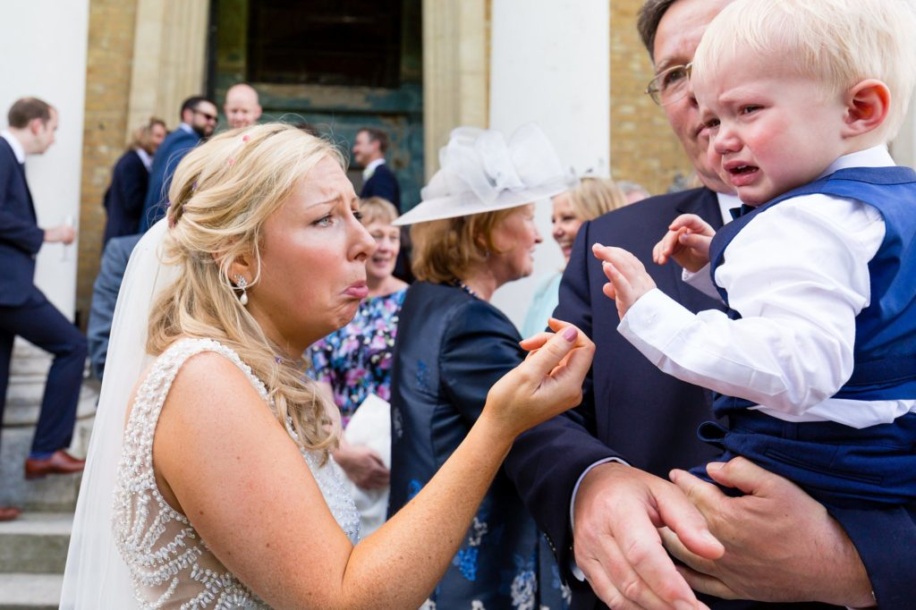 Bride makes sad face at little boy at Asylum wedding.