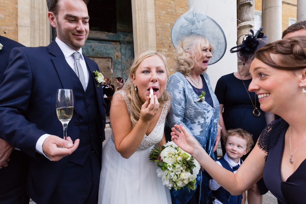 Bride puts on lipstick whilst the groom holds champagne glass.