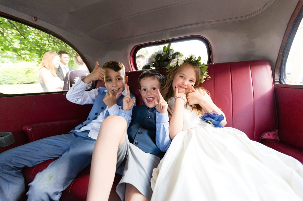 Little kids sitting in back of vintage car at wedding making thumbs up at Asylum wedding.