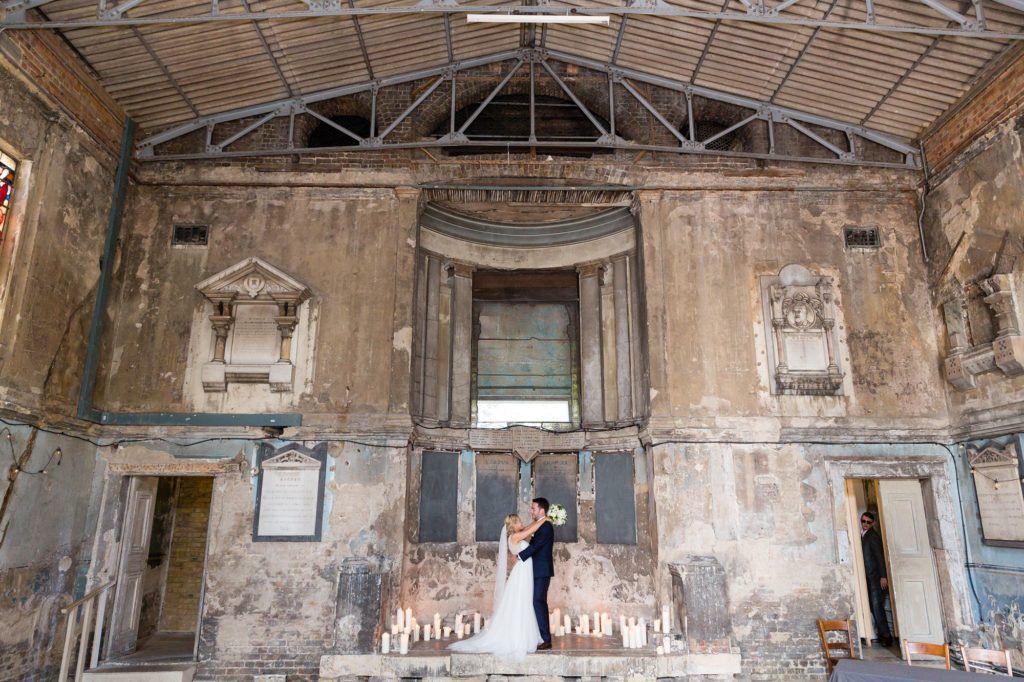 Wide shot of bride and groom inside Asylum wedding venue with crumbling walls.