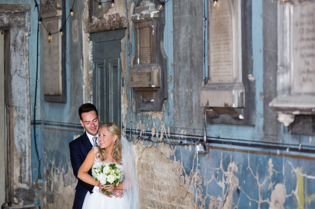 Bride & groom next to crumbling pale blue wall in de-consecrated church at The Asylum in London.
