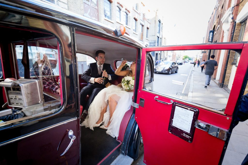 Fun bride necks prosecco in vintage car at London wedding.