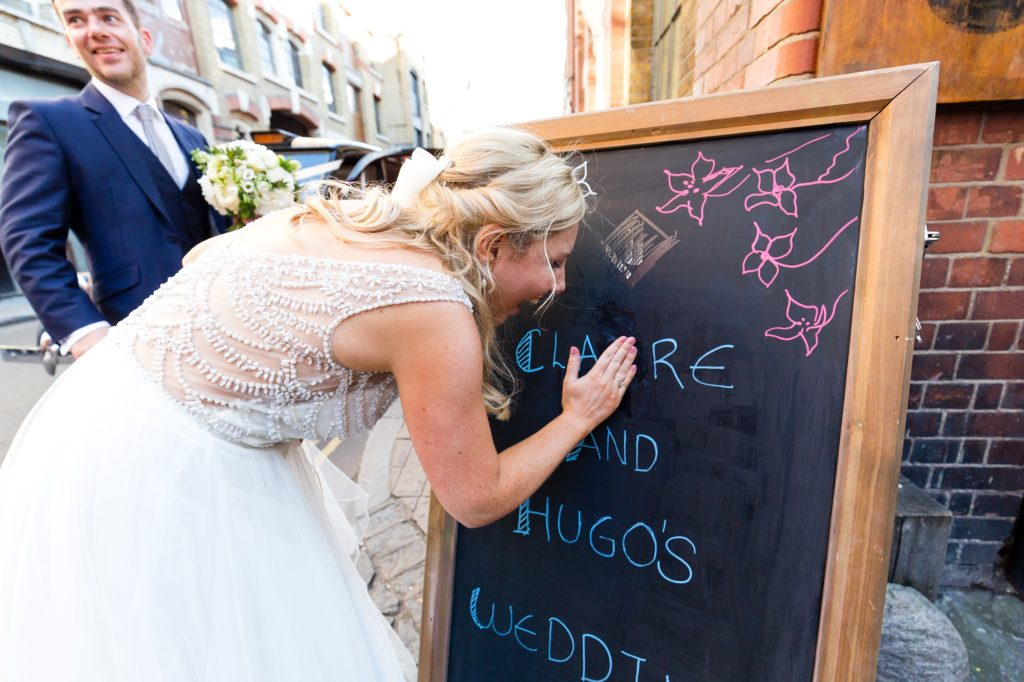 Bride rubs out wrong letter on chalkboard at her wedding.