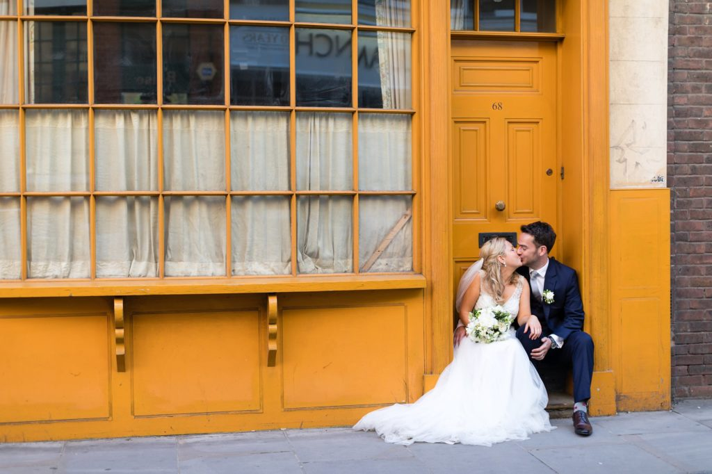 Bride & Groom kissing in doorway in front of yellow London building.