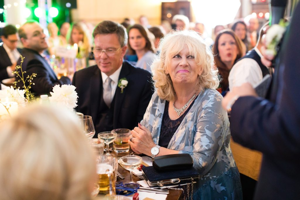 Groom's mum smiles during wedding speeches.