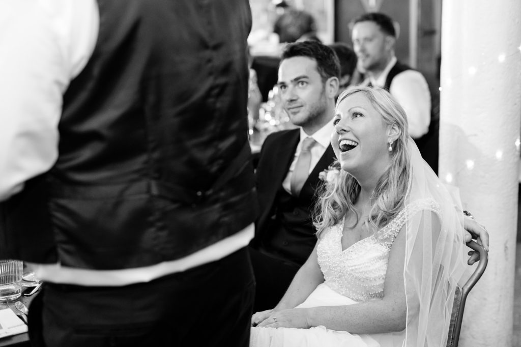 Bride smiles at dad during wedding speeches.
