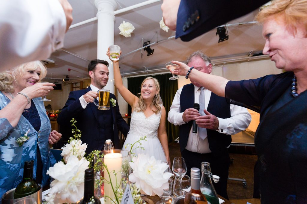 Bride, groom & gusts raise glasses of beer and champagne for a toast.