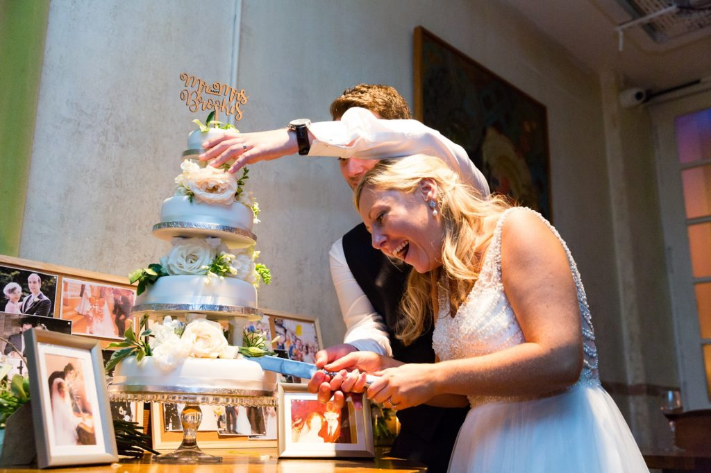 Groom hold cake from falling down at London wedding during cake cutting.