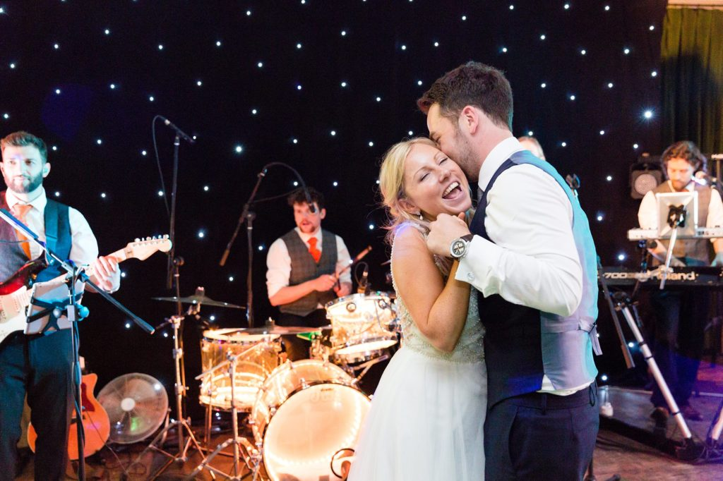 Groom kisses bride on cheek at London wedding.