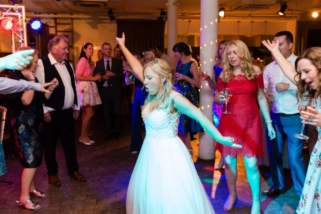 Bride does John Travolta disco move on the dance floor at her London wedding.