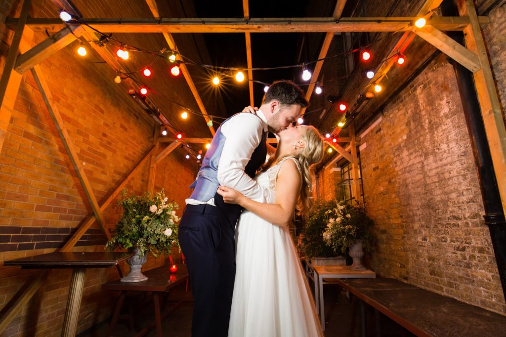 Wedding Photography at Asylum Chapel kiss under festoons at night.