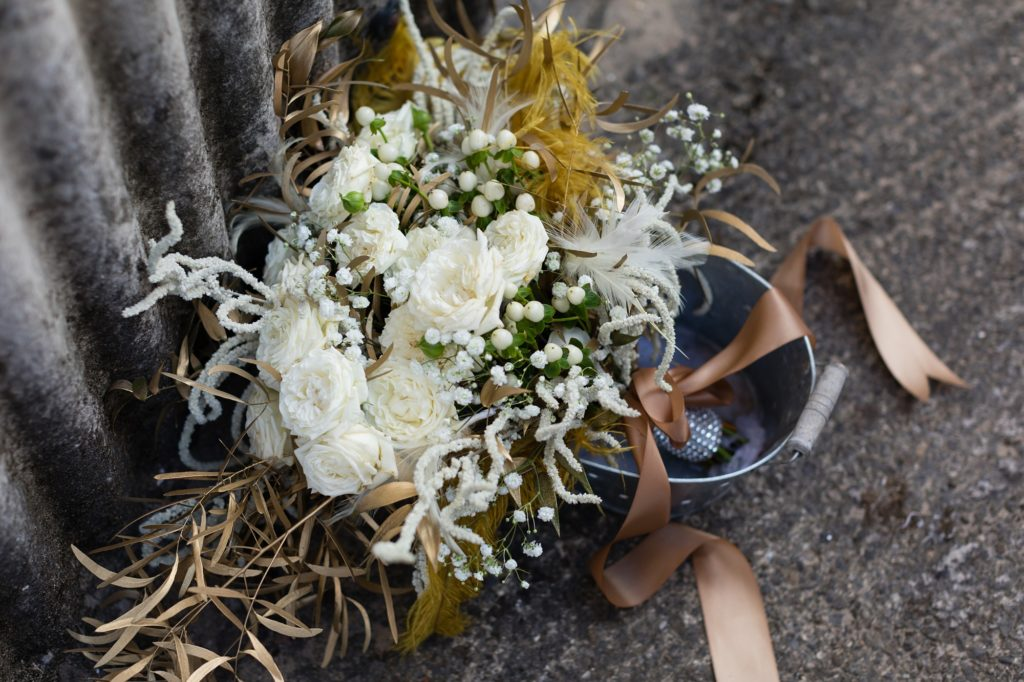 White and brown rustic bouquet in tin bucket.