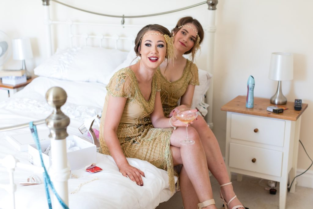 Flapper style bridesmaids in gold coloured dresses.