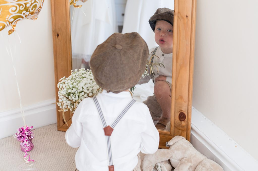 Peaky Blinders styled pageboy making silly faces in mirror at Sandburn Hall Wedding.