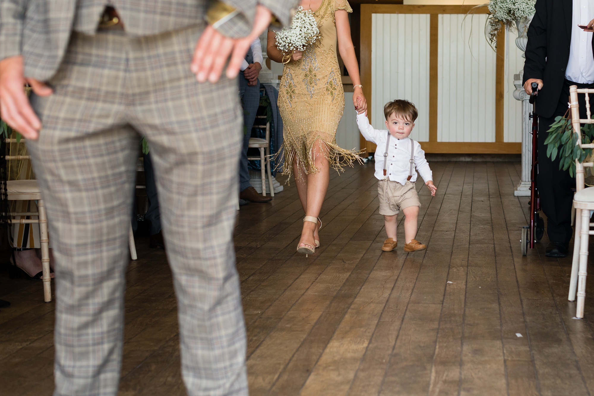 Adorable pageboy in braces walks up aisle at Sandburn Hall wedding.