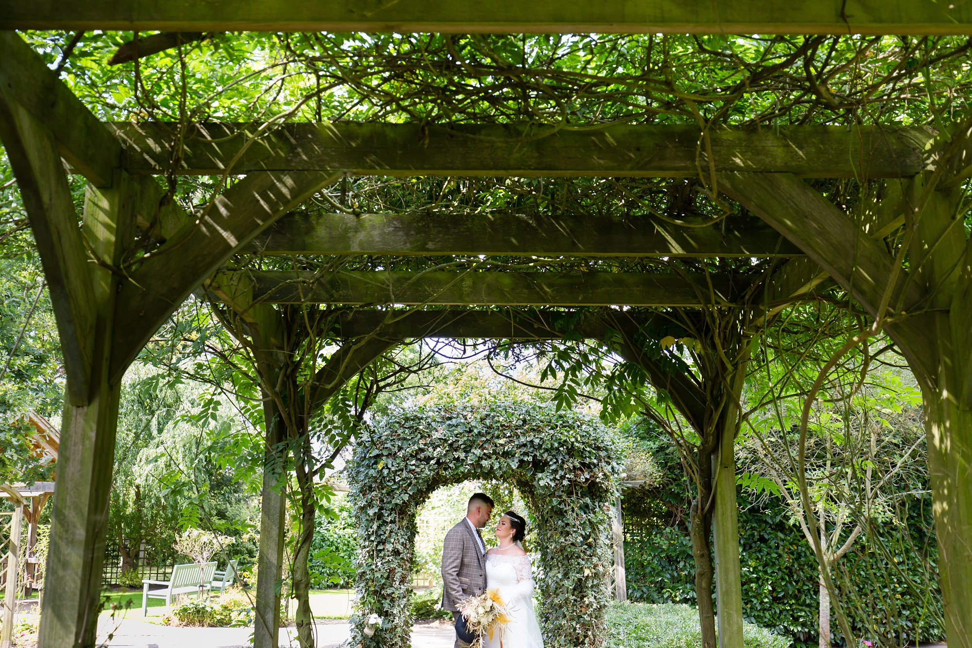 Bride & Groom standing under arbour at Sandburn Hall wedding.