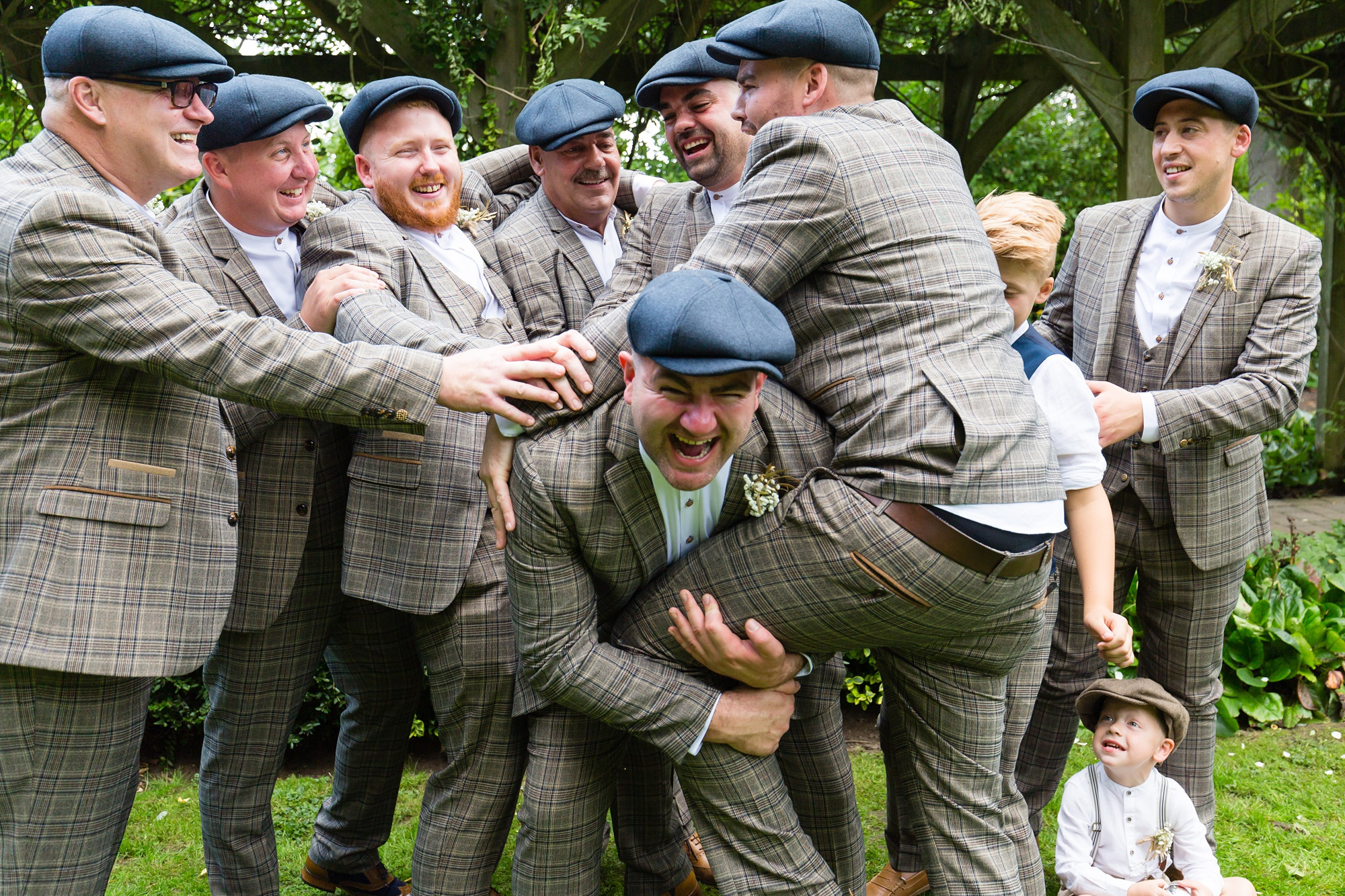 Groomsmen having fun and laughing when taking group photos at Sandburn Hall wedding.