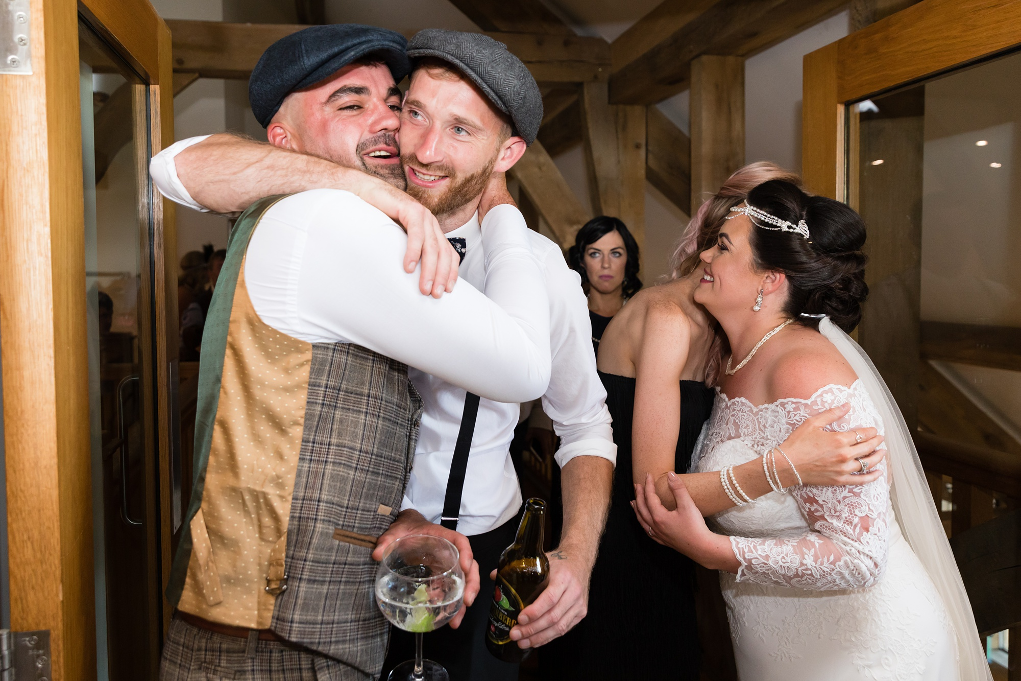 Groom gives big hug to guest at Sandburn Hall wedding.