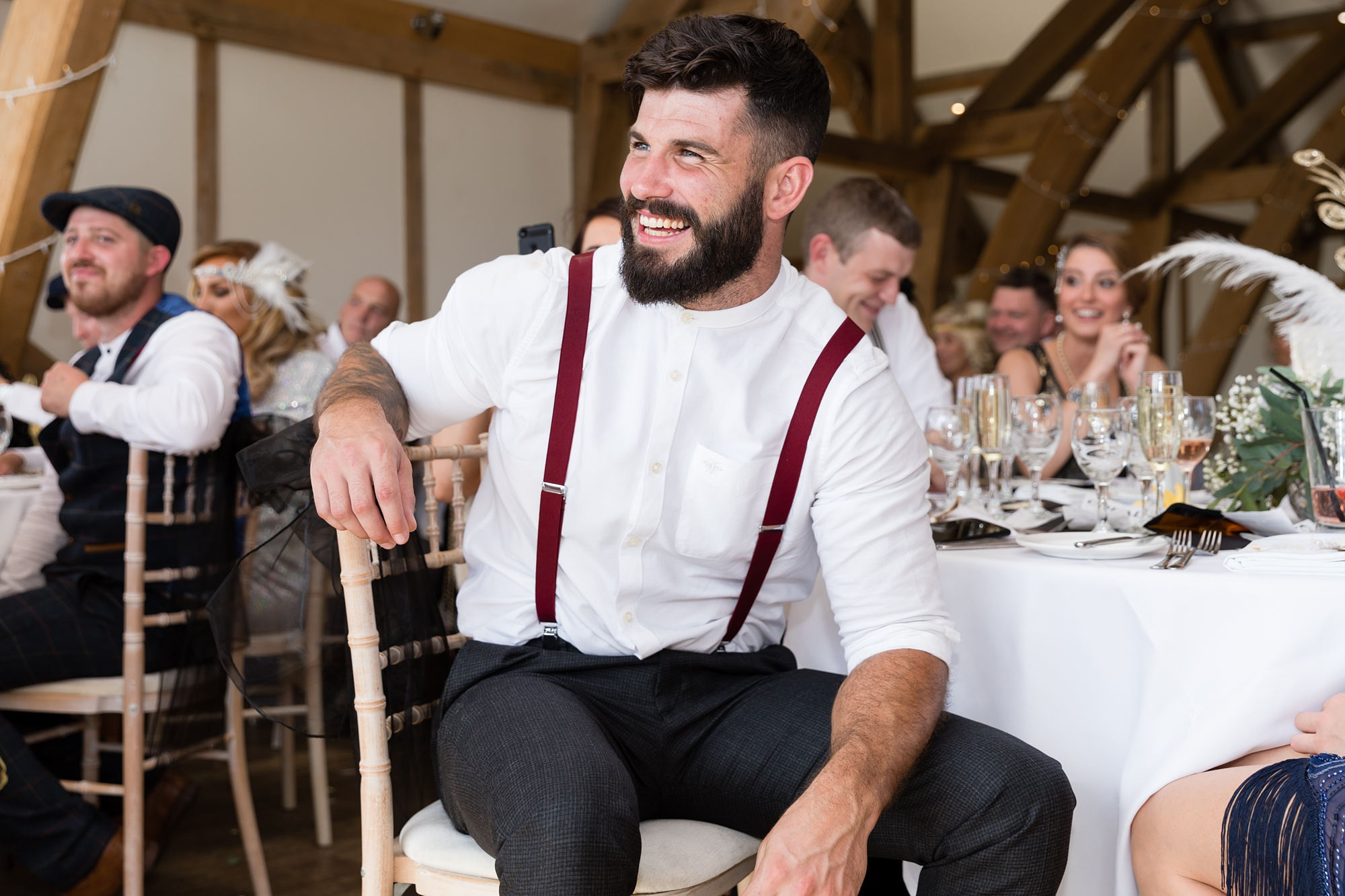 Guest with beard & braces laughing during speeches at Sandburn Hall Wedding.