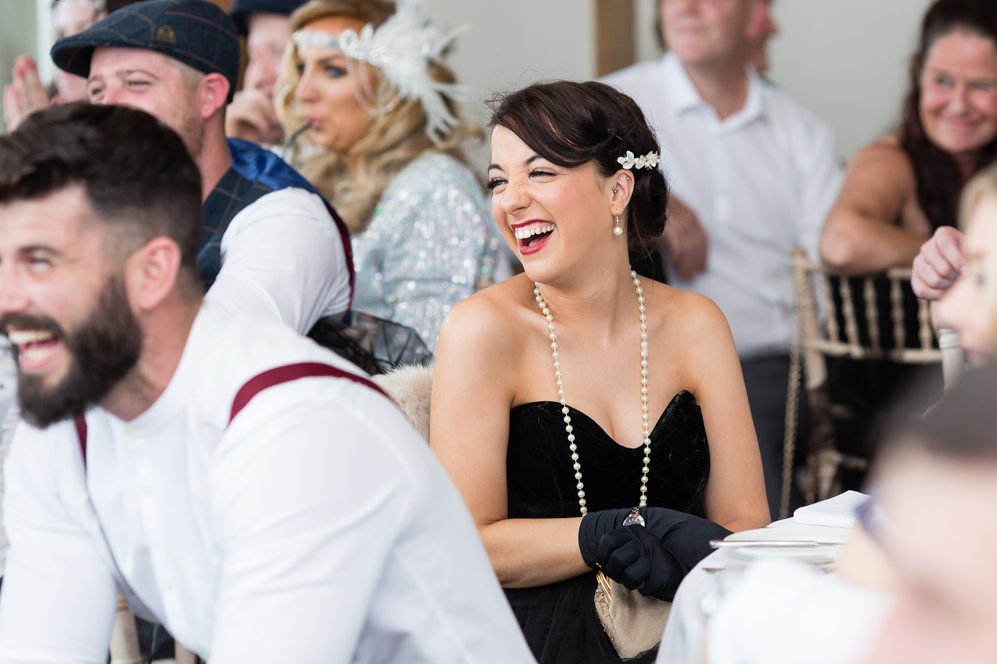 Wedding guest wearing flapper style dress and laughing during speeches.