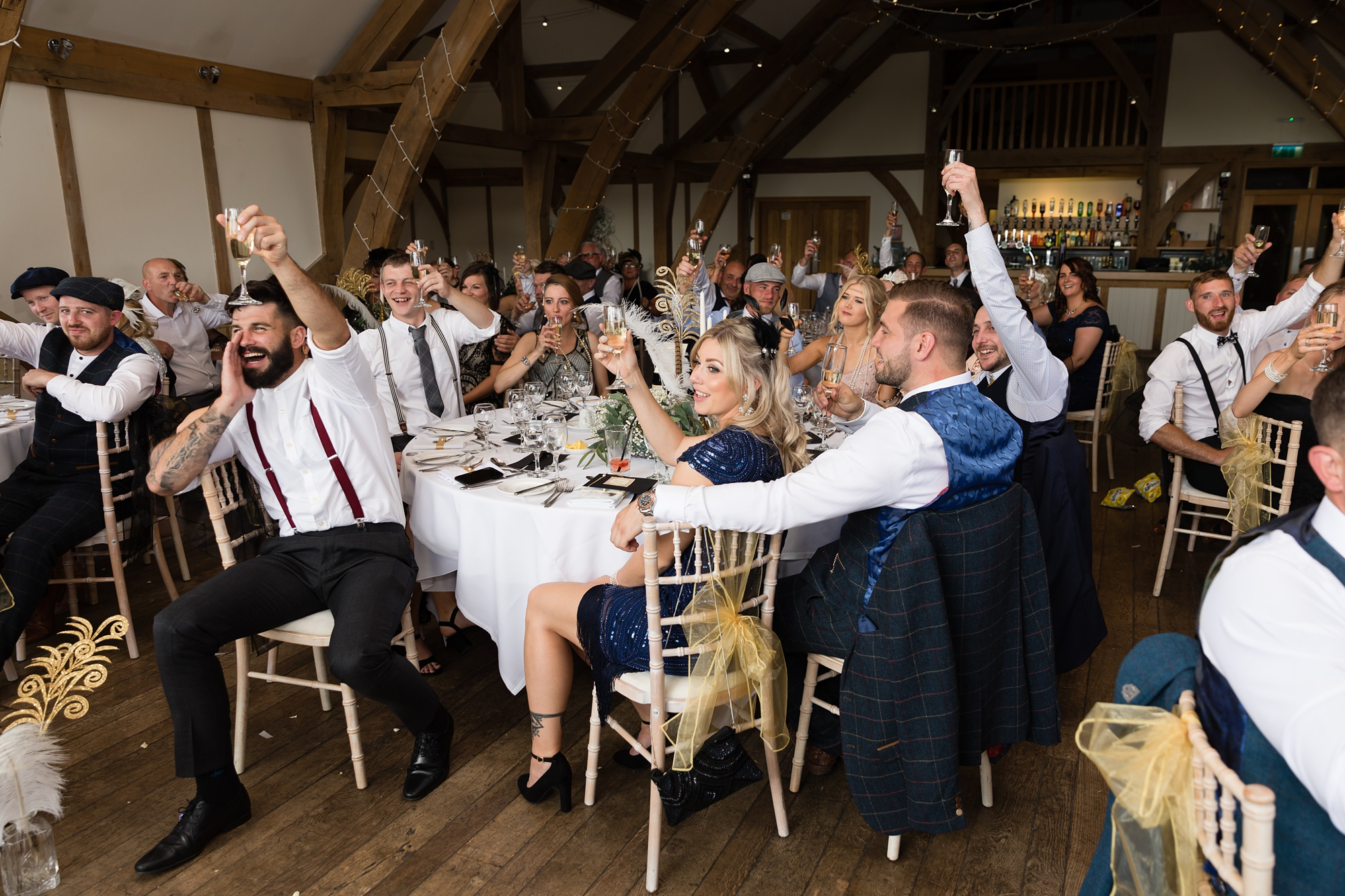 Wide shot of guests giving a toast at Sandburn Hall wedding.