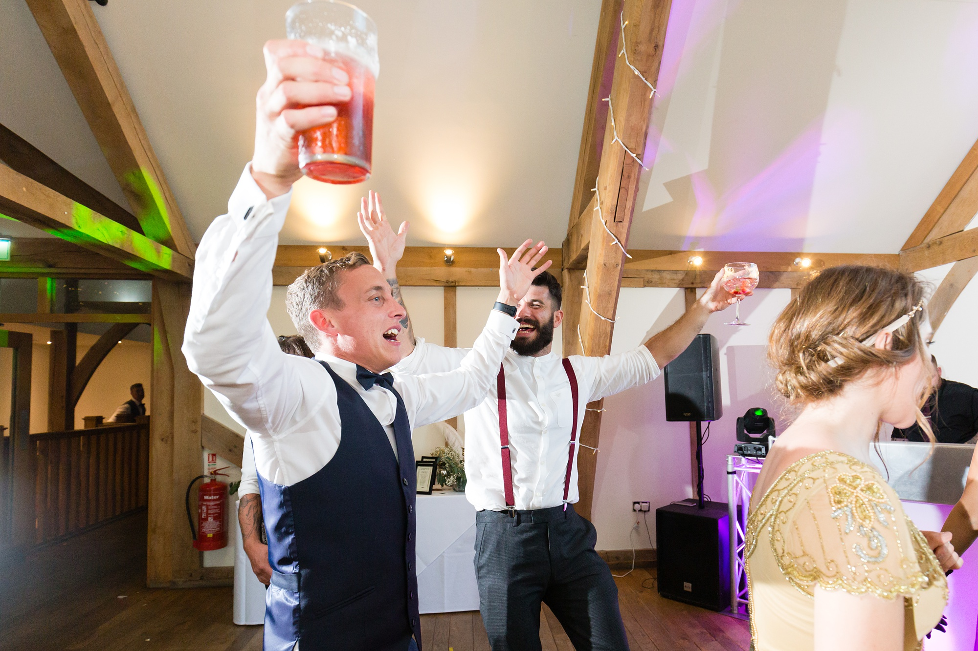 Guests dance holding their beer at wedding.