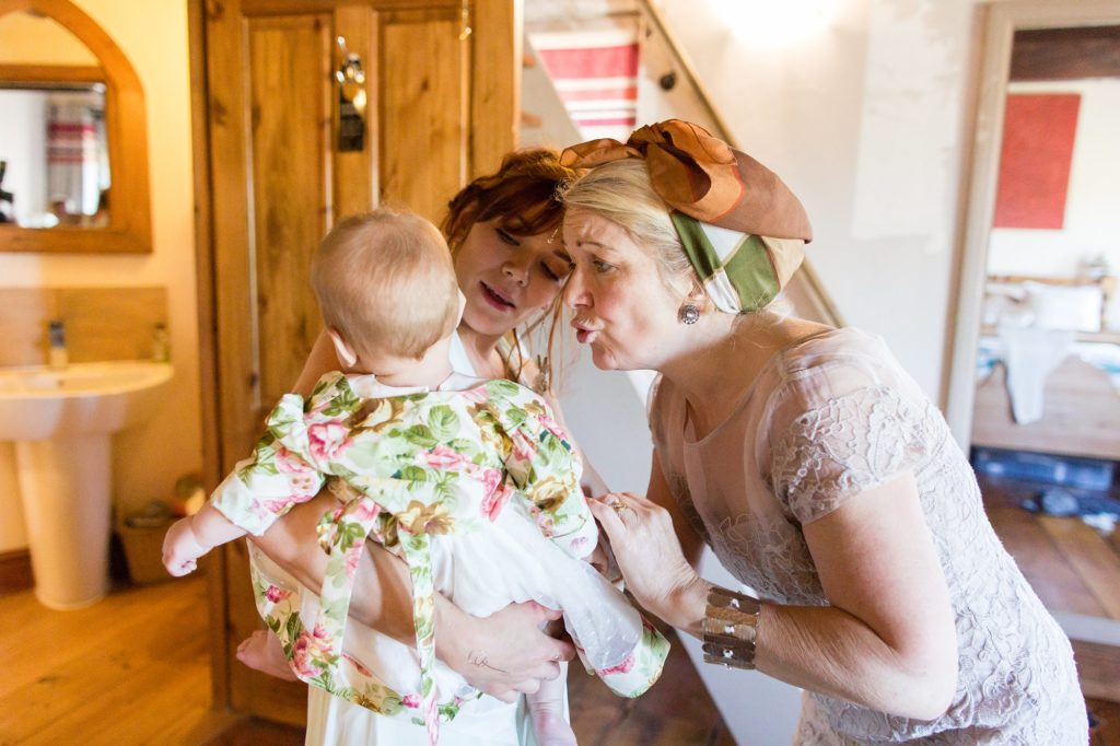 Mum and grandmother make faces to baby flower girl at wedding.