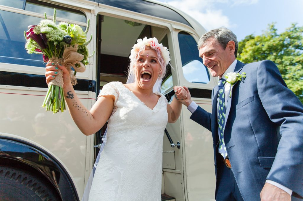 Bride has a huge, happy smile as she exits the bus for her wedding at East Riddlesden Hall.