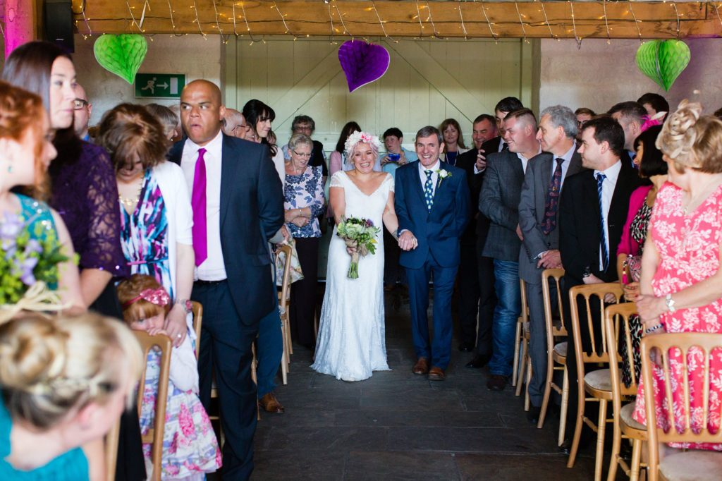 Alternative bride with pink hair and flower crown walks up aisle at East Riddlesden Hall wedding.