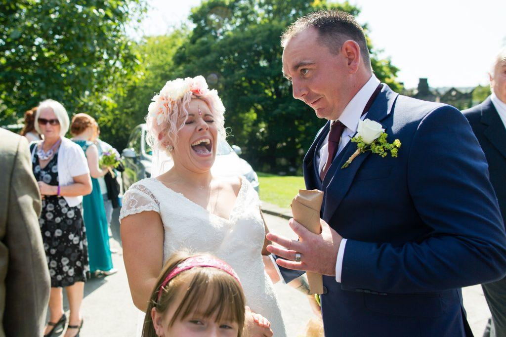 Bride smiles and laughs with guest at East Riddlesden Hall