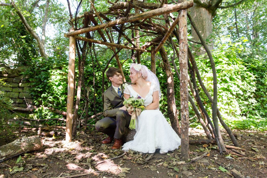 Bride & groom sit inside woodland den at East Riddlesden Hall wedding.