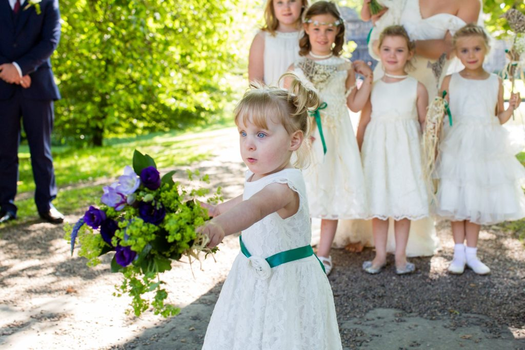 Little flower girl running away during group photos at Yorkshire wedding.