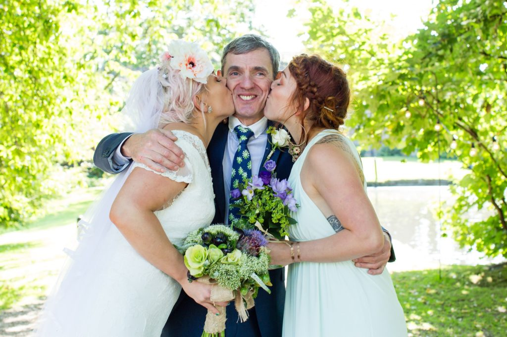 Bride and twin sister kiss her dad on the cheeks at East Riddlesden Hall