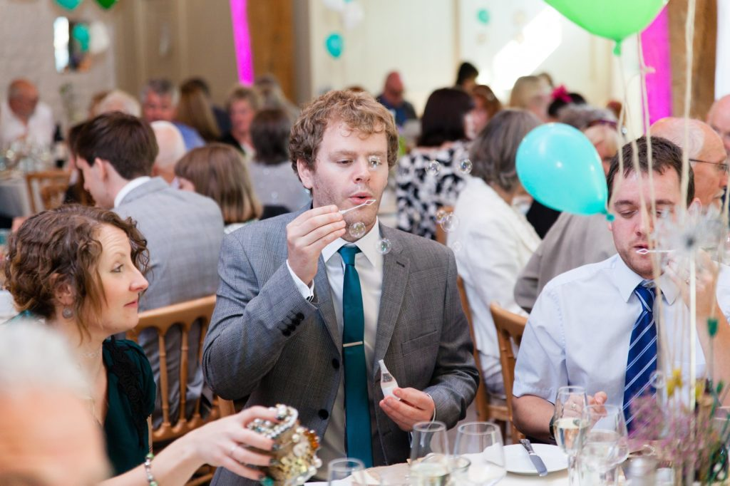 Guest at colourful wedding blows bubbles.