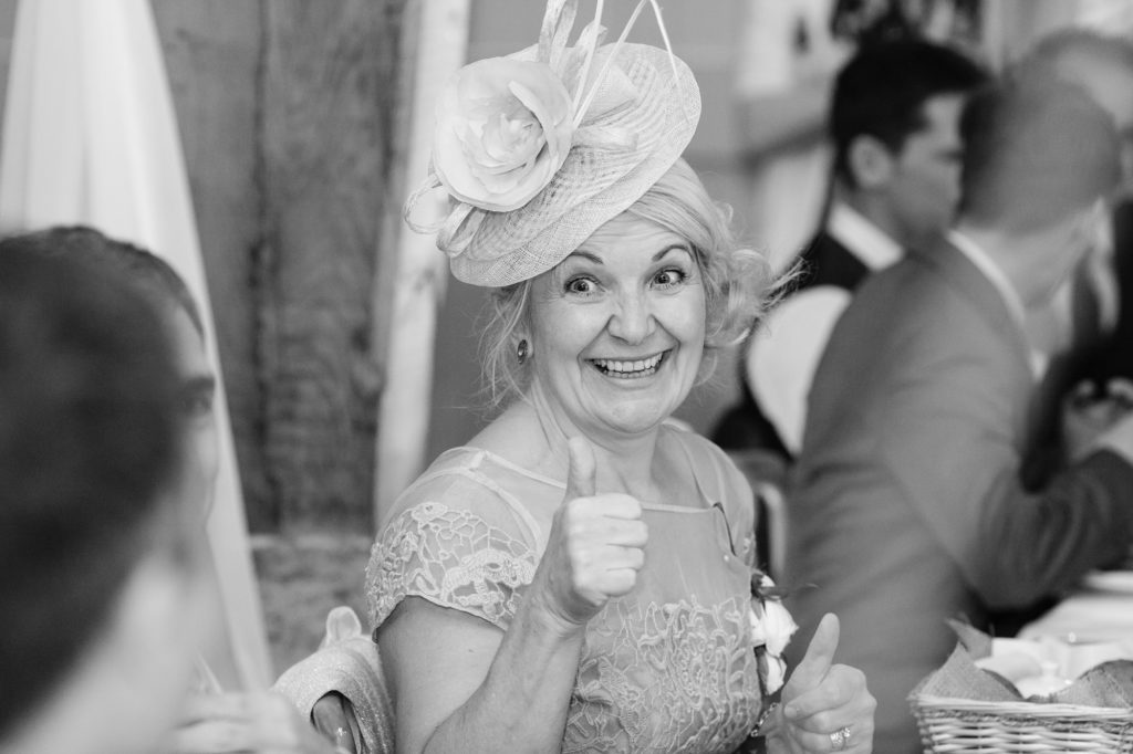 Bride's mother gives thumb's up and smiles at East Riddlesden Hall wedding.