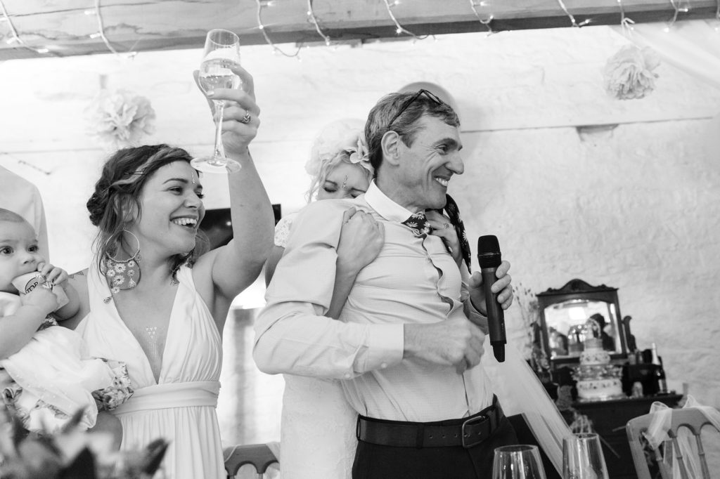 Bride gives dad big hug whilst sister toasts with wine glass at fun and emotional wedding in Yorkshire.