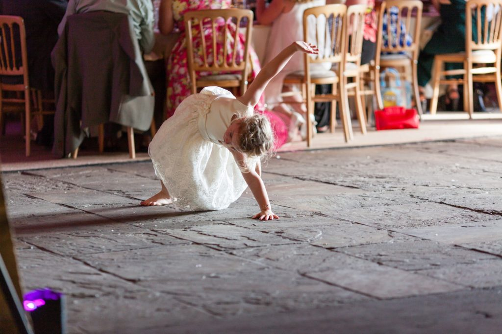 Little flower girl does cartwheel behind speeches.