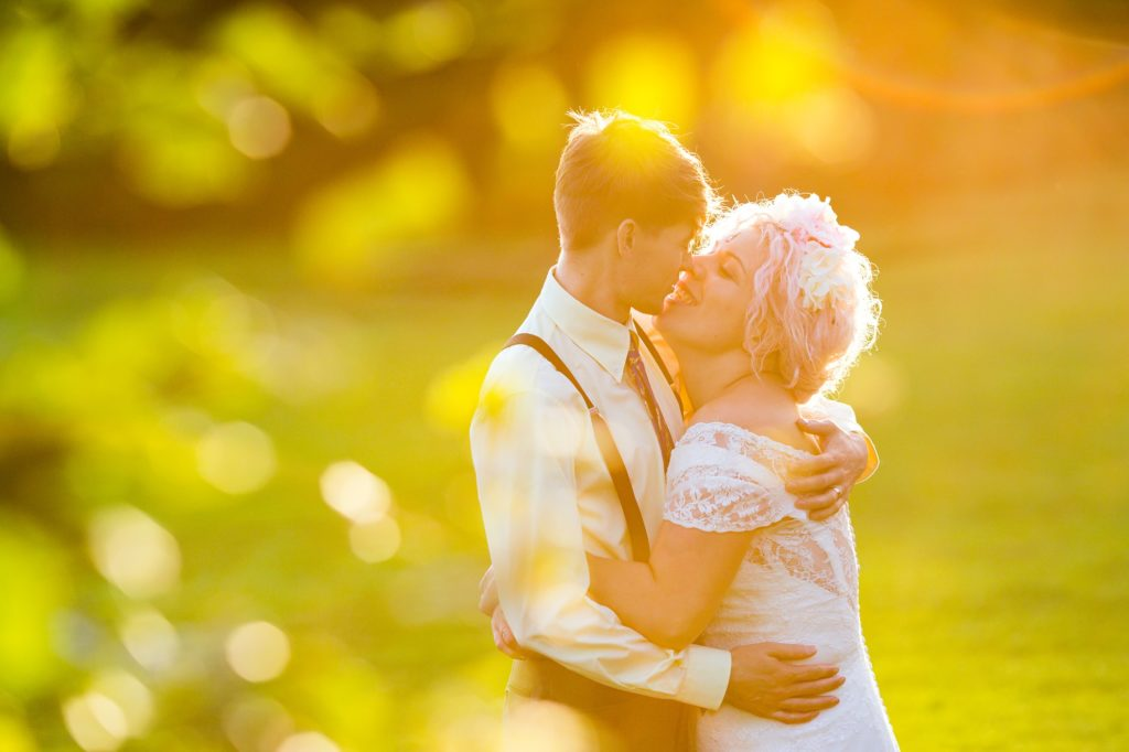Bride in flower crown snuggles groom wearing braces in sunset golden hour at East Riddlesden Hall.