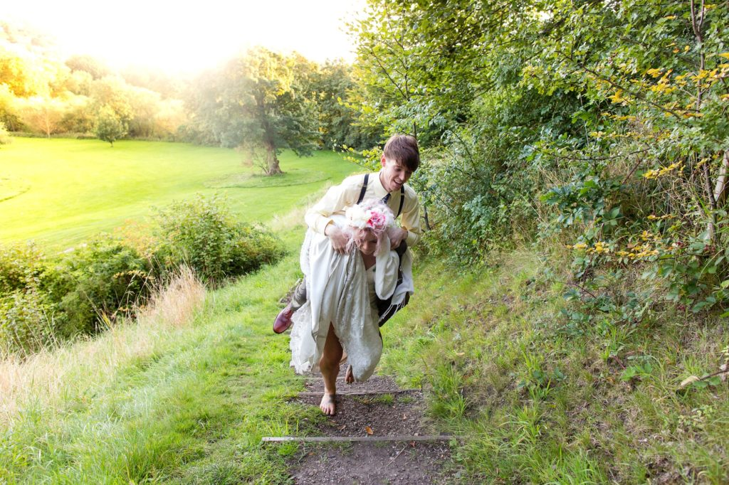 Bride gives groom at piggyback ride in bare feet at fun wedding.