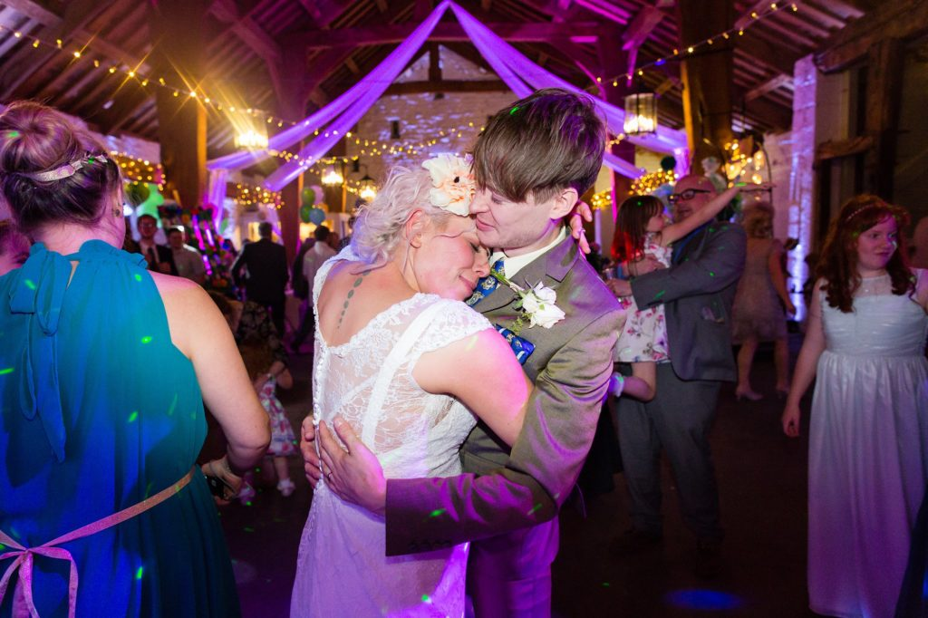Bride and groom hug on dance floor with purple lighting.