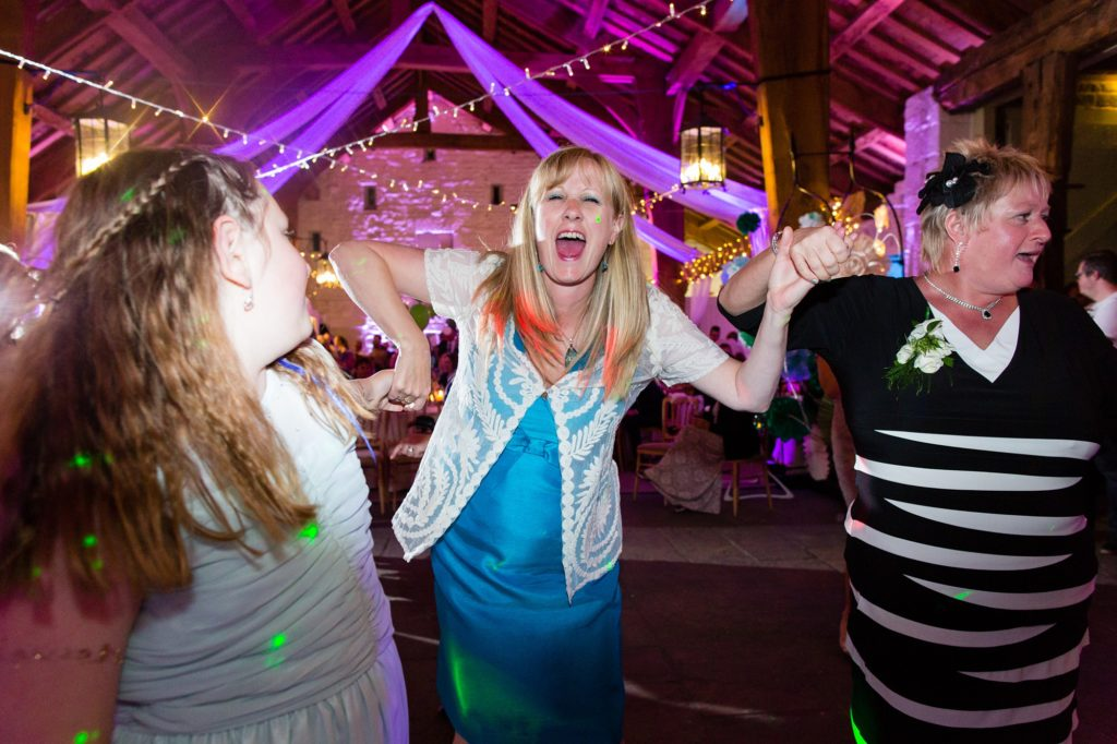 Guests laughing and dancing at party with purple uplighters.