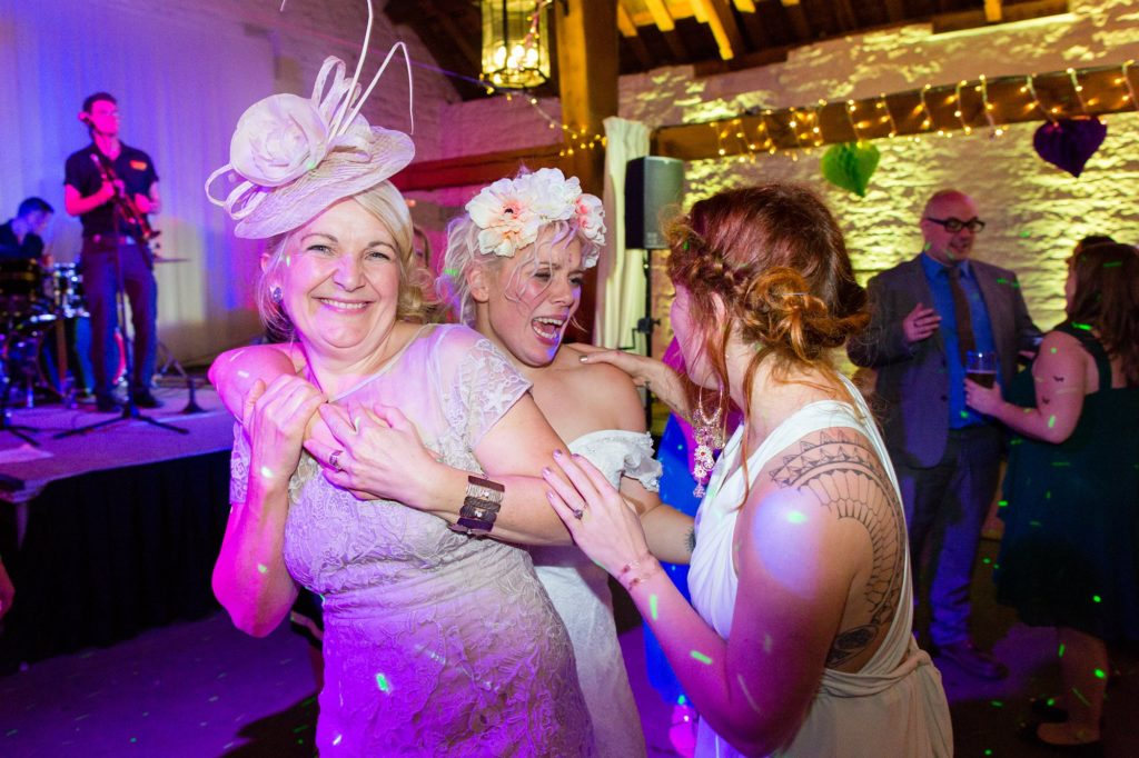 Bride hugs mum on dance floor at East Riddlesden Hall wedding.